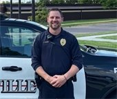 Roseville Deputy Chief Adams, in front of RPD Squad.